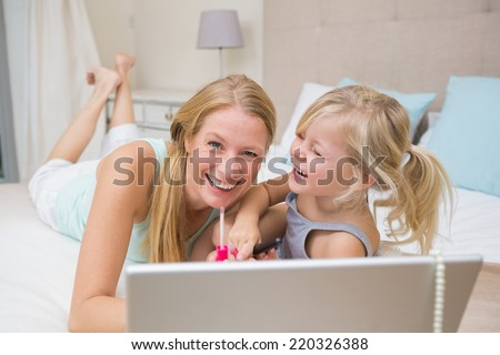 Cute little girl and mother on bed using laptop at home in the bedroom - stock photo