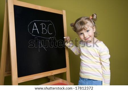Cute little girl at blackboard - stock photo