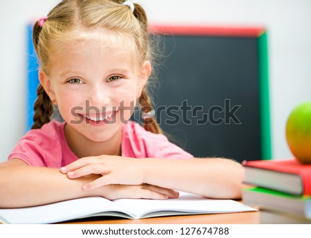 cute little girl at the desk with the books - stock photo