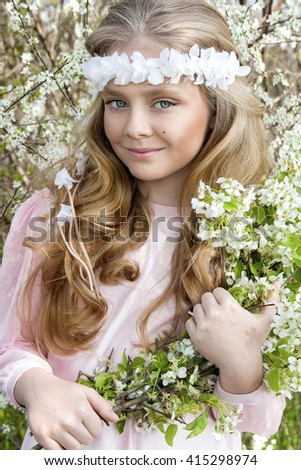 cute, little girl blonde little princess with amazing eyes, standing in a garden on a background of white flowers, wreath on his head and the hands holding white flowers, the spring and holy communion - stock photo