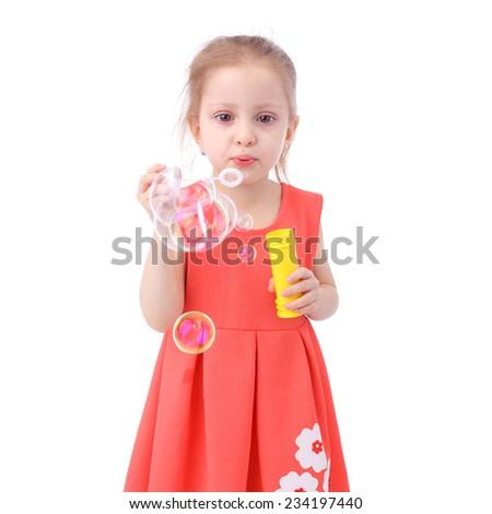 cute little girl blowing soap bubbles - stock photo