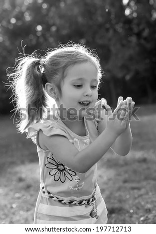 Cute little girl blowing soap bubbles on nature background