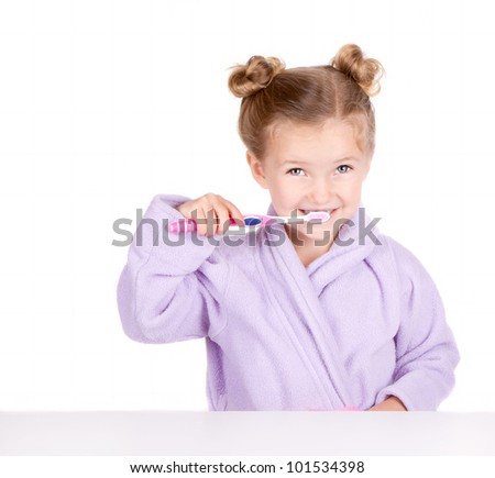 Cute little girl brushing teeth in bathrobe isolated on white - stock photo