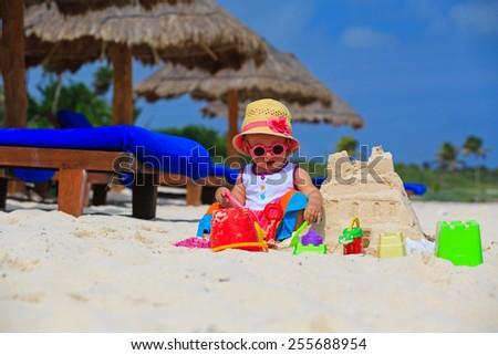 cute little girl building sandcastle on tropical beach - stock photo
