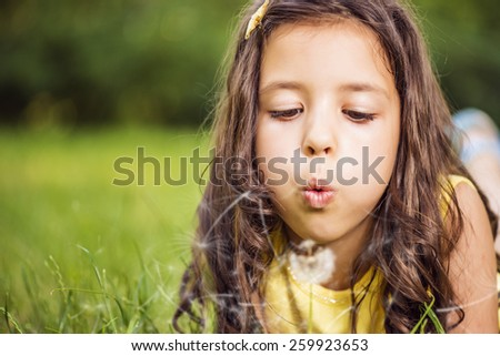 Cute little girl busy blowing Dandelion seeds while relaxing in the park