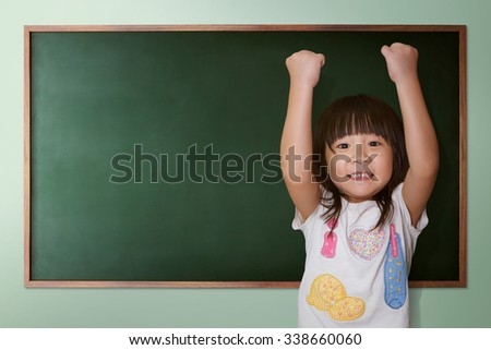 Cute little girl cheering on a background of black school board