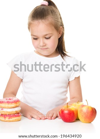 Cute little girl choosing between apples and cake, isolated over white - stock photo
