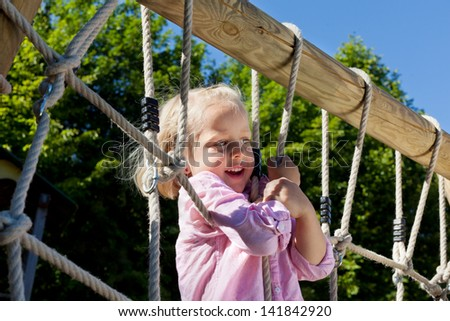 Cute little girl climbing ropes at an outdoor playground clinging on with her hands in the summer sun
