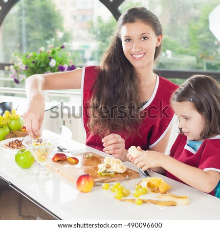 Cute little girl cooking with her sister. Healthy food, cooking healthy salad with fruits ingredients. Mom and daughter cooking together. Recipe food for baby or child