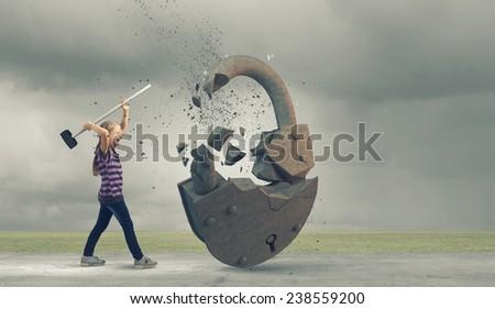 Cute little girl crushing stone lock with hammer - stock photo