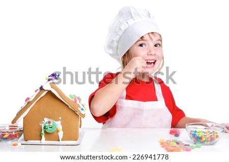 Cute Little Girl Decorating a Gingerbread House on a White Background for Christmas wearing a chef hat and apron - stock photo