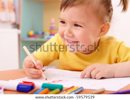 Cute little girl draw with felt-tip pen in preschool - stock photo