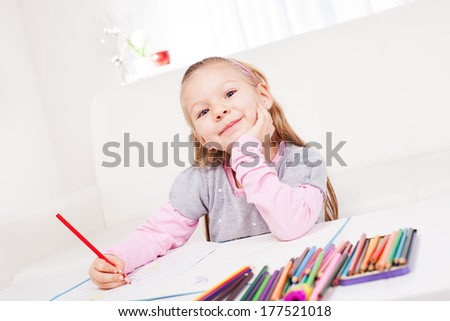 Cute little girl drawing colored pencils at home.