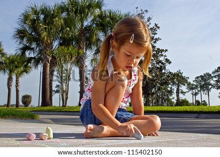 Cute little girl drawing on sidewalk with pastel chalks - stock photo