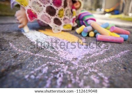 Cute little girl drawing with chalk outdoors - stock photo