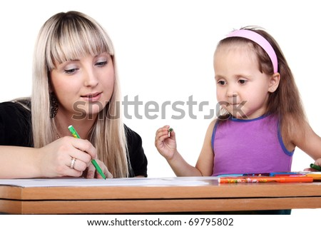 cute little girl drawing with her beautiful mother - stock photo