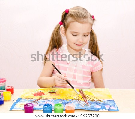 Cute little girl drawing with paint and paintbrush at home