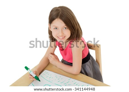 Cute little girl draws felt-tip pen at table.Isolated on white background - stock photo