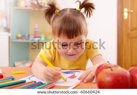 Cute little girl draws with felt-tip pen in preschool - stock photo