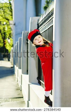Cute little girl dressed in old-style coat posing on the street, sunny day - stock photo