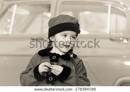 Cute little girl dressed in retro coat posing near oldtimer car, sixties - stock photo