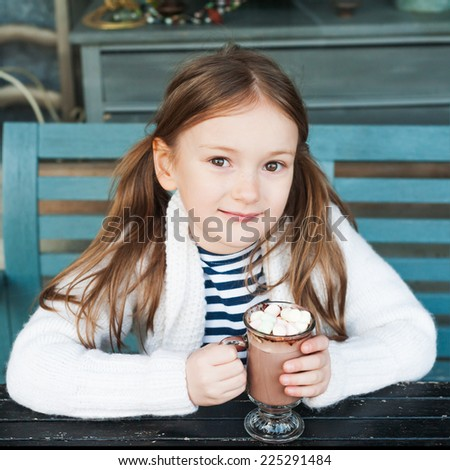 Cute little girl drinking hot chocolate in a cafe on a cold day - stock photo