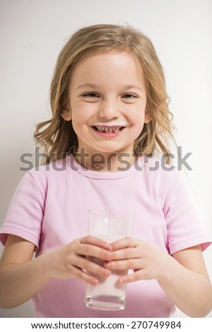 Cute little girl drinking milk on grey background. And looking on camera. - stock photo