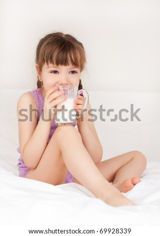 cute little girl drinking milk on the bed at home - stock photo