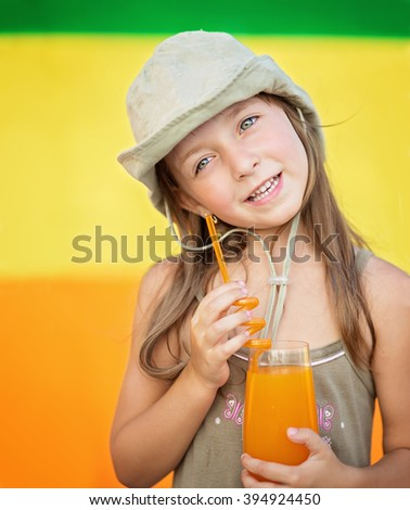 Cute little girl drinking orange juice in the summer outdoors - stock photo