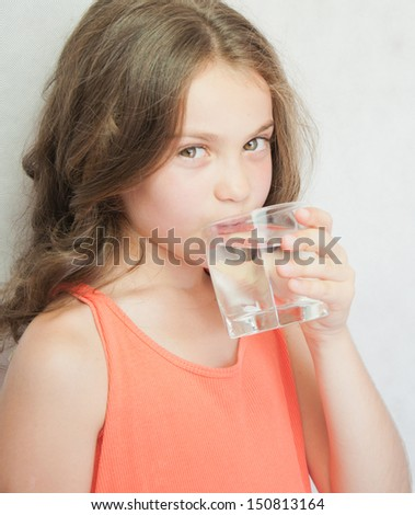 Cute little girl drinking water on the grey background - stock photo