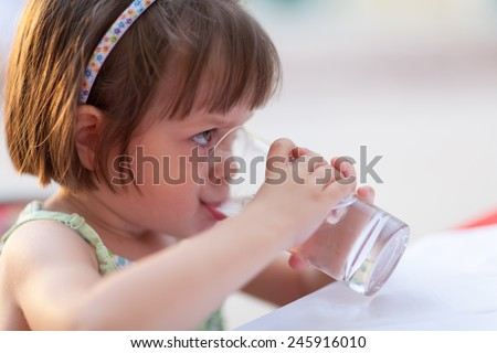 Cute little girl drinking water outdoors - very shallow deep of field (girl's eye is perfectly sharp) - stock photo