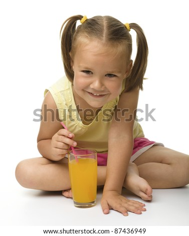 Cute little girl drinks orange juice using drinking straw while sitting on the floor, isolated over white