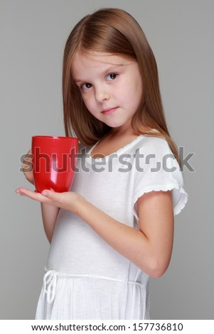 Cute little girl drinks tea from a red cup on a gray background on Food and Drink - stock photo