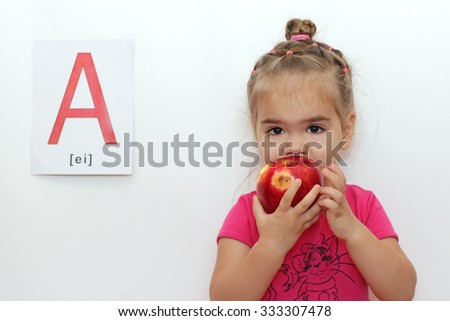 Cute little girl eating a red apple, indoor isolated portrait over the white background with A letter on it - stock photo