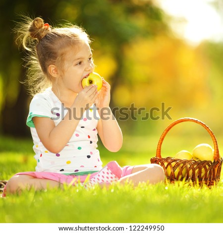 Cute little girl eating apple in the park - stock photo