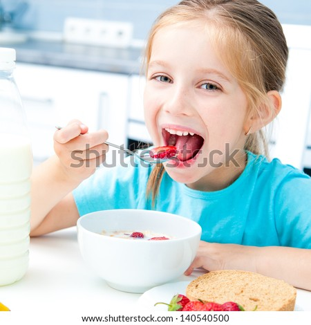 cute little girl eating cereal and strawberries in white kitchen - stock photo