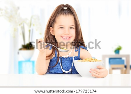 Cute little girl eating cereal from a bowl seated on table at home