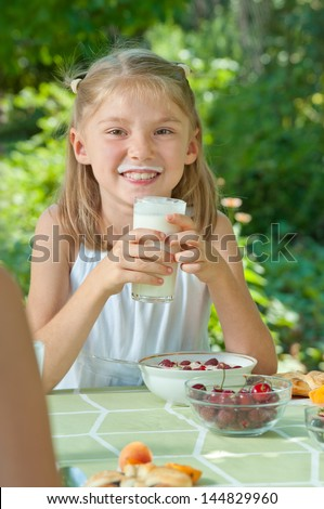 Cute little girl eating cereal in the garden