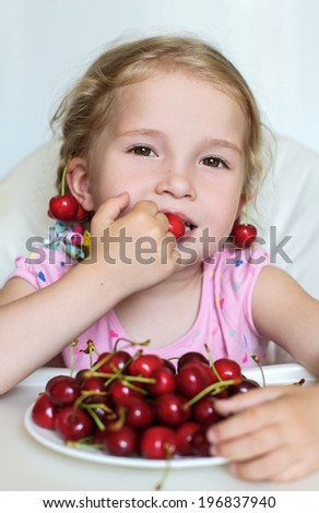 cute little girl eating cherries on white background - stock photo