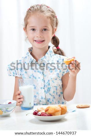 Cute little girl eating  cottage cheese and milk at home