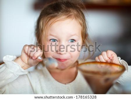 Cute little girl eating dessert at restaurant - stock photo