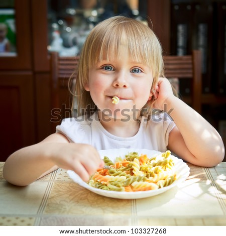 Cute little girl eating Fusilli - stock photo