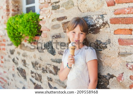 Cute little girl eating ice cream on a sunny day, outdoors