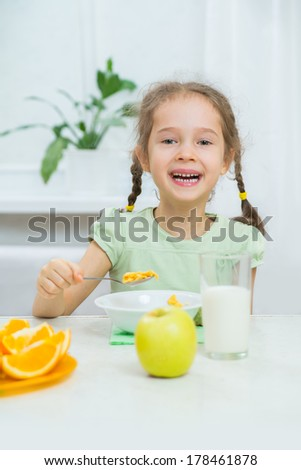 Cute little girl eating muesli with milk and fresh fruits - stock photo