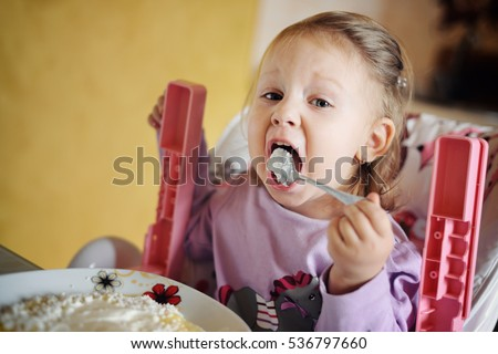Cute little girl eating porridge