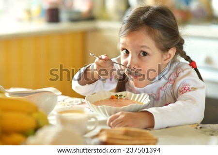 cute little girl eating soup at home - stock photo