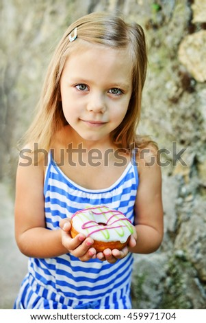 Cute little girl eating sweet donuts outdoors - stock photo
