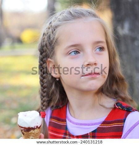 cute little girl eating the ice-cream in the park