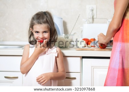 Cute little girl eating tomato while helping her mother in the kitchen - stock photo