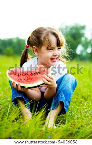 cute little girl eating  water-melon on the grass in summertime - stock photo